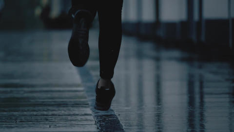 Super slow motion telephoto shot of young woman's feet running on wet pavement Footage
