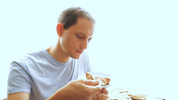 Young man trying, tasting and eating portion piece of tiramisu cake on plate at Footage