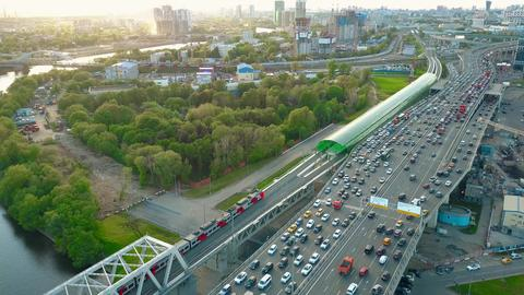 Aerial shot of heavy traffic jam and moving commuter trains in the rush hour Fotografía