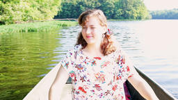 Happy young woman rowing boat on lake in Virginia during summer with warm, soft Footage
