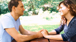 Young couple sitting, talking, holding hands at picnic table in outdoor park Footage