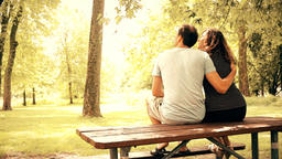 Back of young couple sitting on picnic table in outdoor park hugging, embracing Footage