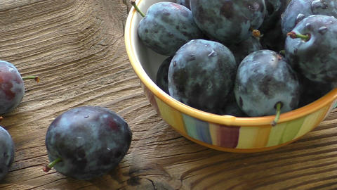 A bowl of ripe blue plums on a dark wooden background Footage