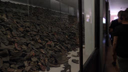 Visitors are watching collection of shoes at Auschwitz I concentration camp Footage