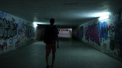 Man going through an underpass subway with graffiti art on the walls ภาพวิดีโอ
