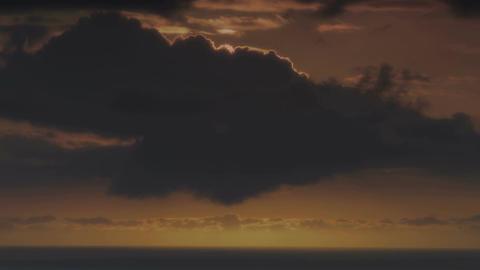 Bright orange sun going down behind dark clouds tim lapse Footage