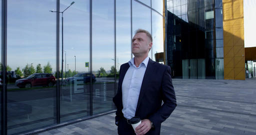 Mature businessman walking with coffee Footage