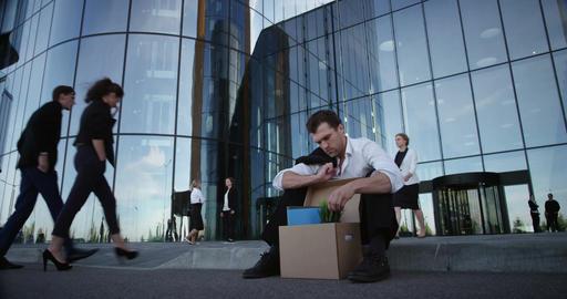 Fired businessman sitting on street Footage