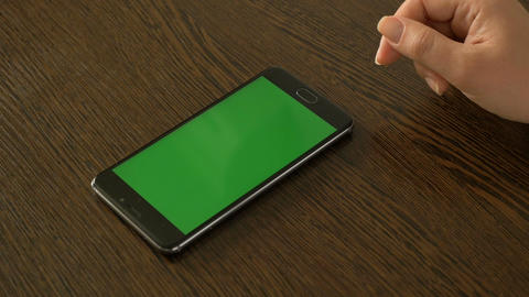 A female hand and a mobile phone with a green screen that lies on the table Image