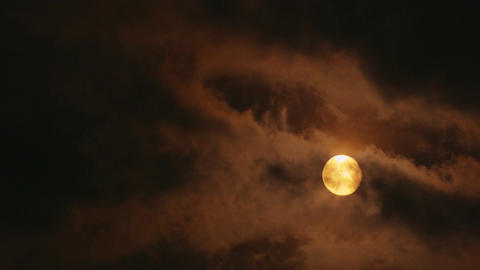 Full yellow moon shining through clouds Footage