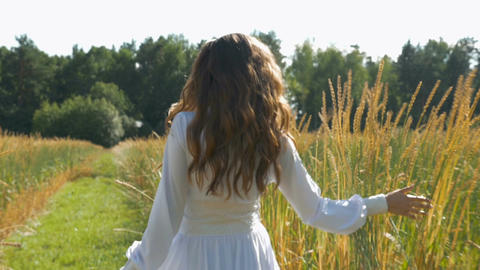 A young beautiful woman in a white dress is spinning on a field with wheat. Slow Footage