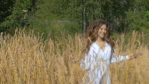 A girl in a white dress runs across the field with wheat Footage