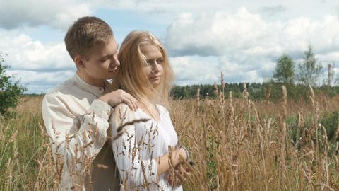 Young blond woman and her boyfriend are hugging on the field with wheat Footage