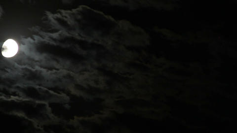 The moon moves on the night sky in the clouds Footage
