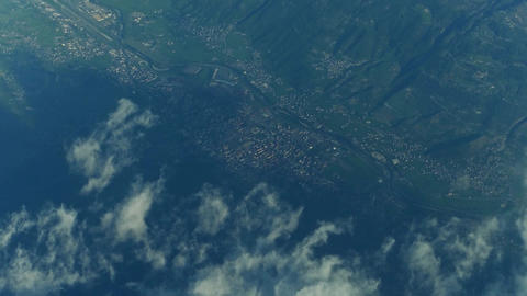 Mountain peaks, clouds, distant airport and alpine towns in a valley Footage