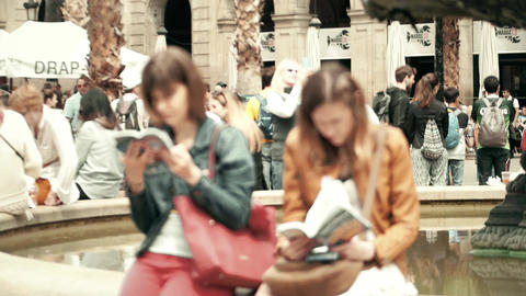 BARCELONA, SPAIN - APRIL, 16, 2017. Two young women reading city tourist guide Footage