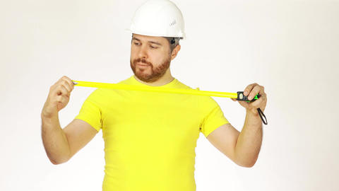 Cheerful construction engineer or architect in yellow tshirtusing measure tape Footage