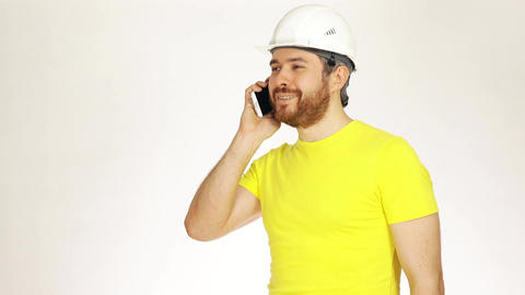 Handsome construction engineer or architect in yellow tshirt talking on his cell Footage