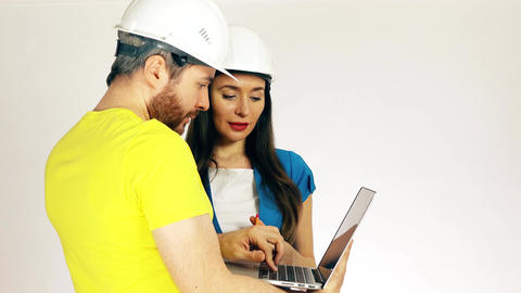 Male and female construction engineers discussing project and using the laptop Footage
