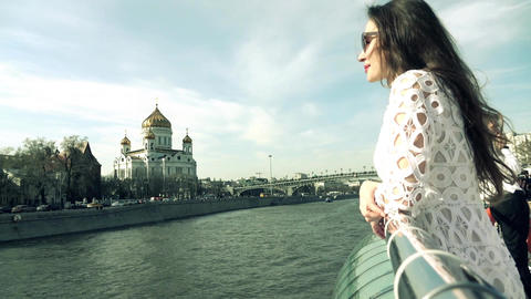 Brunette woman in white dress looking at Christ the Savior Cathedral in Moscow Footage