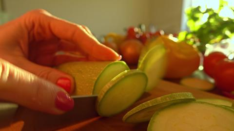 Woman cutting zucchini on a wooden board. Healthy eating and cooking at home フォト