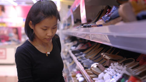 Young Thai Lady picking shoes at super market Footage