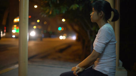 Young Asian girl waiting at bus stop in night city Filmmaterial