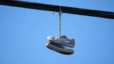 Video of pair of shoes hang tossed telephone wire in 4K Footage