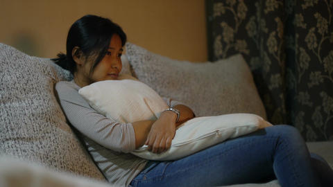 Pretty Asian girl hugs pillow and watches TV Footage