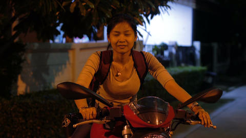 Smiling Thai girl sits on motorbike Footage