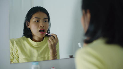 Young Thai Woman applying liquid lipstick in front of mirror Footage