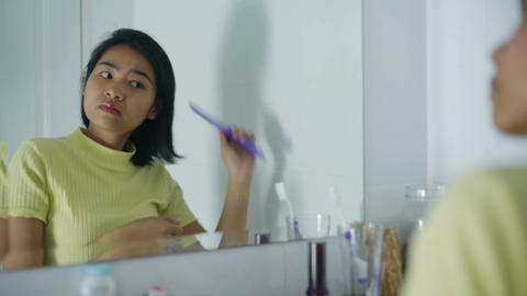 Young Thai woman combing her hair and looking into mirror Footage