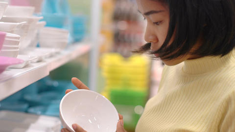 Young Asian Woman buying plates in crockery store Live Action