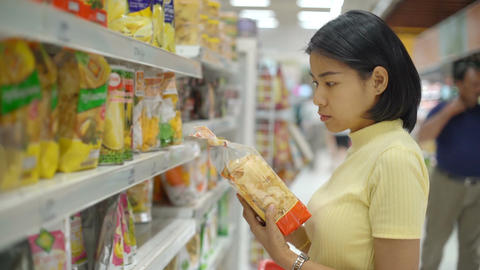 Young Asian Woman buying food in grocery department Live Action