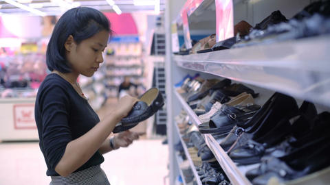 Young Thai Woman choosing shoes in mall Footage