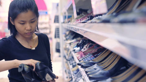 Young Asian Woman shopping at shoes store Footage