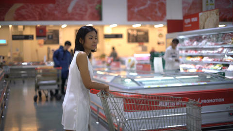 Young Thai lady with shopping trolley walks in supermarket Acción en vivo