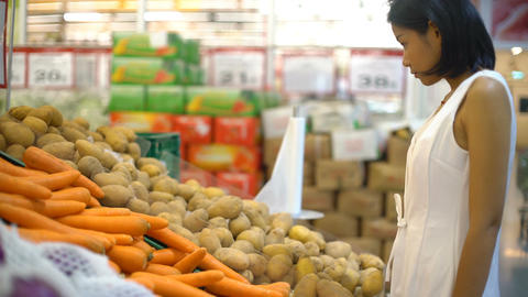 Lady sniffing unwashed potatoes and sneezing in supermarket Footage