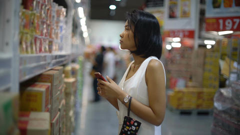 Young Asian Lady near shelves in hypermarket Footage