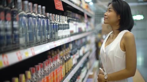 Lady smiling and choosing alcoholic beverage in supermarket Footage