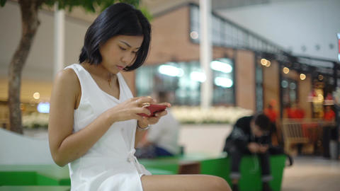 Young Thai Lady sitting in mall and using smartphone Footage