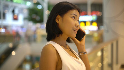 Happy Young Asian Lady talking on smartphone in shopping mall Footage