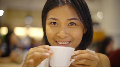 Portrait of young woman drinking hot coffee at restaurant Footage