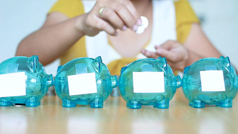 Hands of woman putting money coin into 4 clear piggy bank with blank white paper Footage