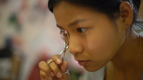 Young Thai Woman using eyelash curler close-up Footage