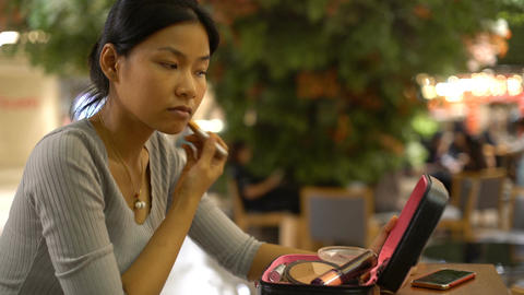 Asian Lady with cosmetic bag applies powder on her neck Footage