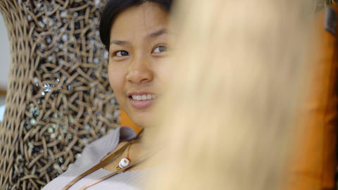 Portrait of smiling young Asian Girl sits on wicker chair Footage