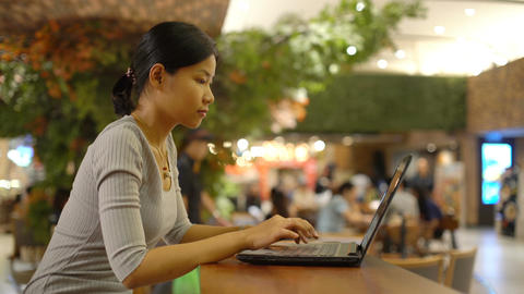 Young Thai Woman typing on laptop computer in shopping mall Footage