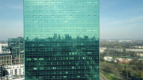 Modern office building facade reflecting cityscape on a sunny day Footage