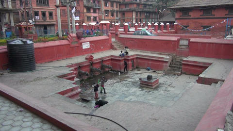 children pouring water into container from public fountain, Kathmandu, Nepal Footage